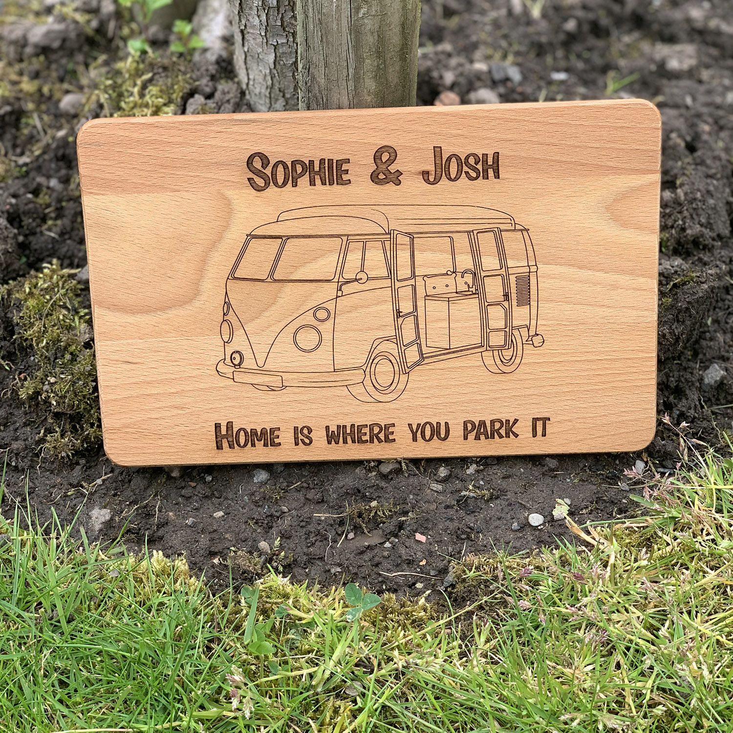 Our personalised campervan chopping board looking great in front of a tree making a fab campervan accessory gift