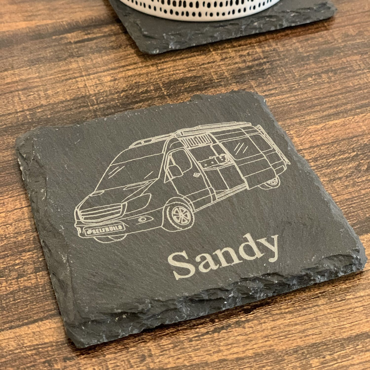 Our campervan coaster in slate on a table with a sprinter on it and personalised message